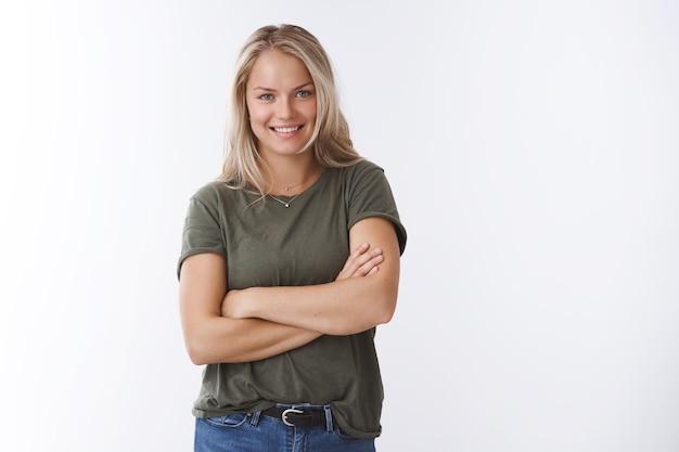 Tente morder meu recorde. retrato de autoconfiante atrevida jovem loira caucasiana com camiseta verde-oliva, cruzando as mãos sobre o corpo, sorrindo ousado e confiante, garantindo que pode levar tudo sob controle