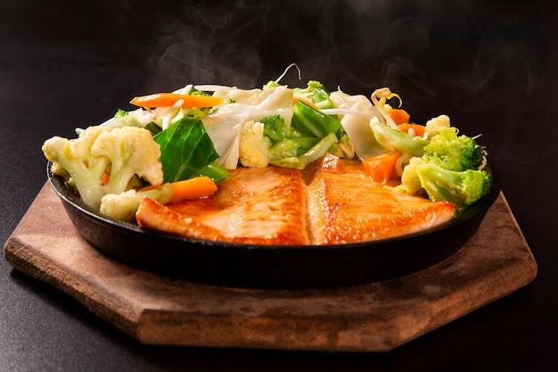 Teppanyaki deliciosa comida de salmão com pauzinhos e legumes na panela de ferro.