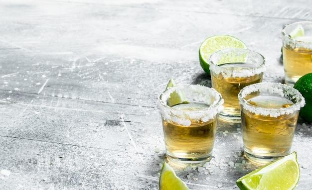 Tequila com fatias de limão. em superfície rústica