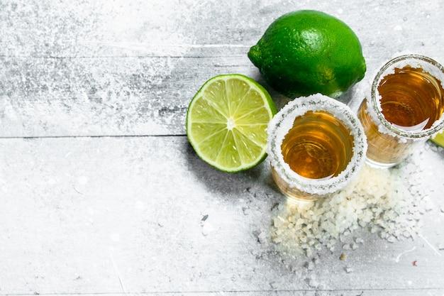 Tequila com limão fresco. na superfície rústica branca