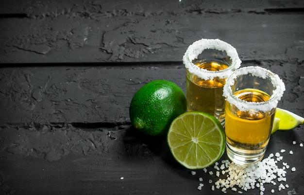 Tequila com sal e limão. em preto rústico