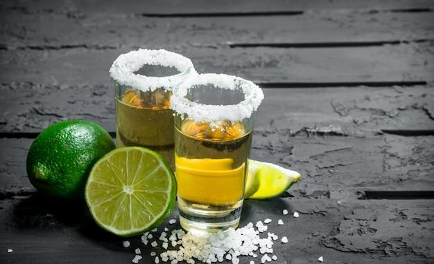 Tequila com sal e limão na mesa rústica preta