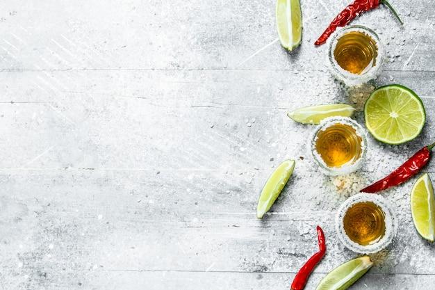 Tequila em um copo com rodelas de limão e pimenta vermelha. em rústico