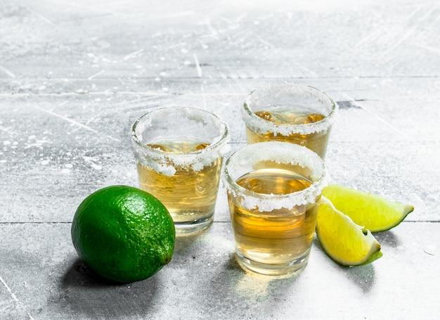 Tequila em um copo com rodelas de limão na mesa rústica branca