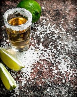 Tequila em um copo com sal e fatias de limão fresco.
