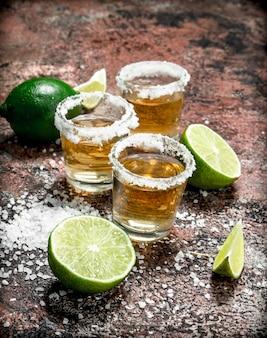 Tequila em um copo com sal e limão fatiado. em rústico