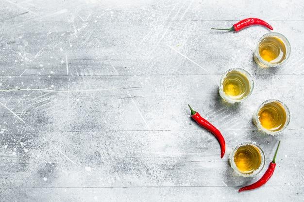 Tequila em um copo de pimenta vermelha quente. em superfície rústica
