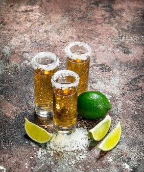 Tequila em um copo de sal e fatias de limão. em superfície rústica
