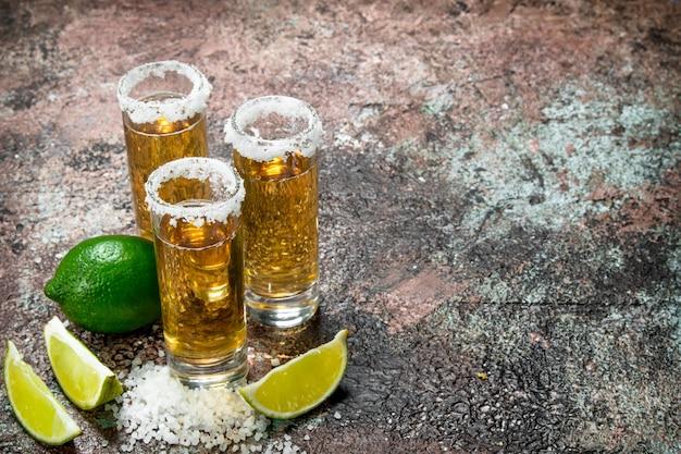 Tequila em um copo de sal e fatias de limão.