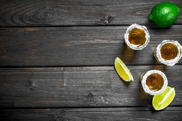 Tequila em um copo de sal e limão na mesa de madeira