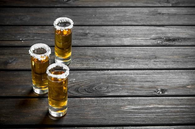Tequila em um copo de sal na mesa de madeira