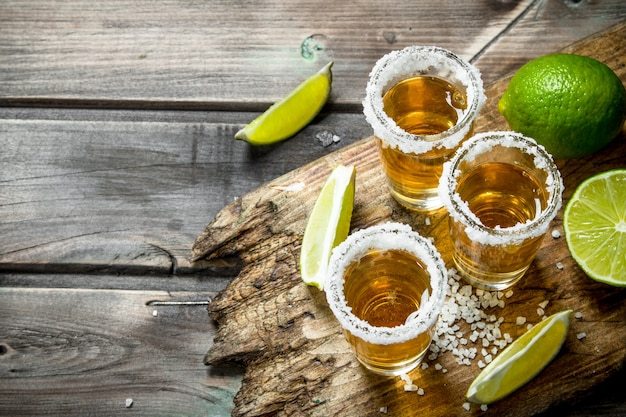 Tequila em um copo de sal na tábua. na mesa de madeira