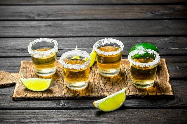 Tequila em um copo em uma placa de corte com fatias de limão. em madeira