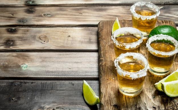 Tequila em um copo em uma placa de corte com fatias de limão. na superfície de madeira