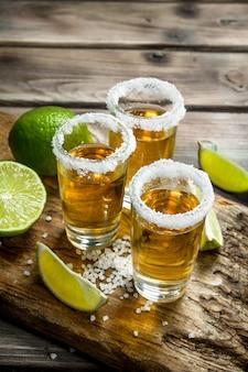Tequila em um copo em uma placa de corte com fatias de limão.