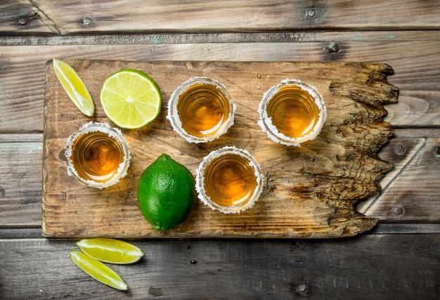 Tequila em um copo em uma placa de corte com limão.