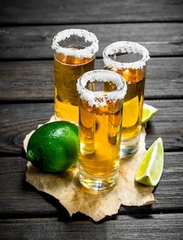 Tequila em um copo no papel com limão. em madeira