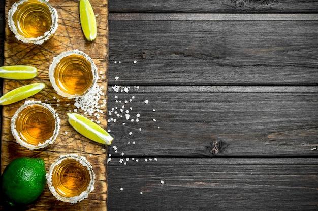 Tequila em uma tábua com fatias de limão fresco. em madeira