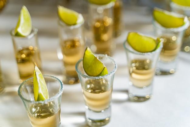 Tequila ou vodka em copos curtos com um pedaço de limão e sal em cima de cada um bem em pé na mesa branca.