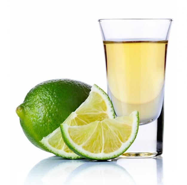 Tequila ouro tiro com limão isolado no branco