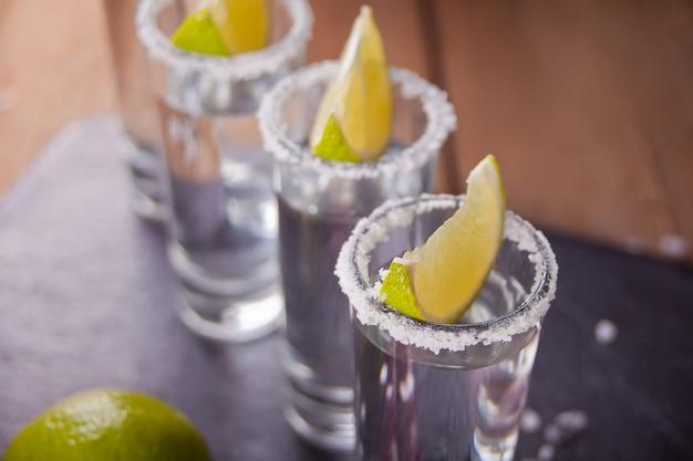 Tequila tiro com limão e sal do mar na bandeja preta, foco seletivo