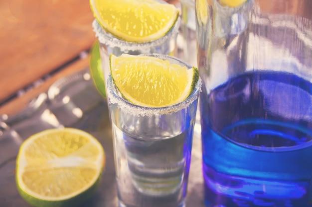 Tequila tiro com limão e sal marinho e garrafa azul na bandeja