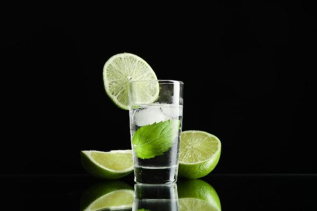 Tequila tiro com limão, hortelã e gelo contra preto