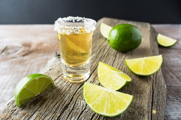 Tequila tiro com limão no fundo de madeira rústico