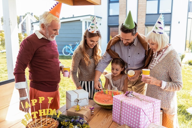 Ter aniversário. mulher loira atenta segurando um copo de papel com a mão esquerda enquanto olha para uma melancia