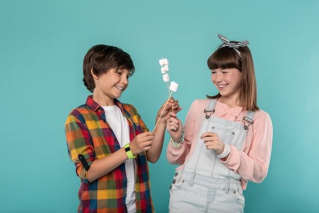 Ter um dente doce. crianças alegres e charmosas ao lado umas das outras comendo biscoitos