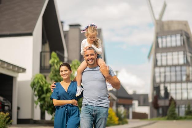 Ter uma caminhada em família. filha adorável sentada no pescoço do pai enquanto a família caminha