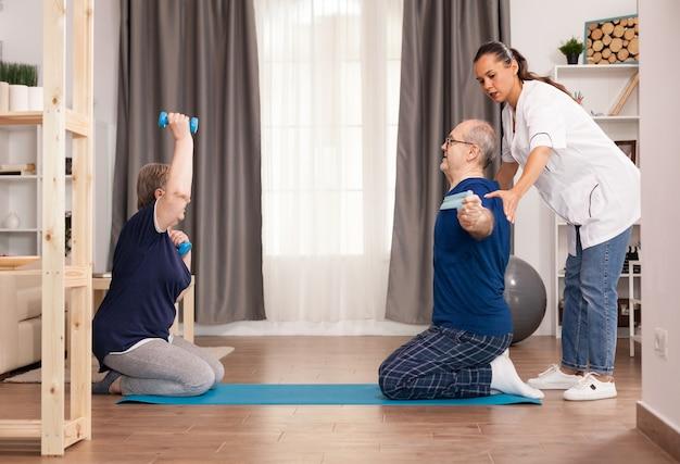 Terapeuta ajudando idosos a se recuperarem após uma intervenção médica.
