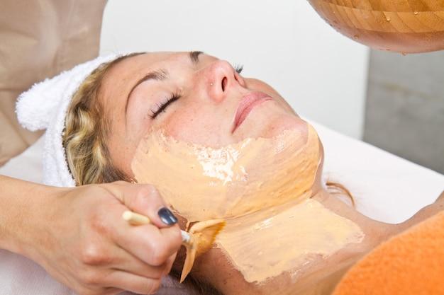 Terapeuta, aplicando, um, máscara rosto, para, um, bonito, mulher jovem, em, como