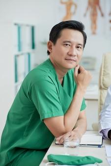 Terapeuta asiática vestindo uniforme verde, sentado na mesa, olhando para o retrato da câmera