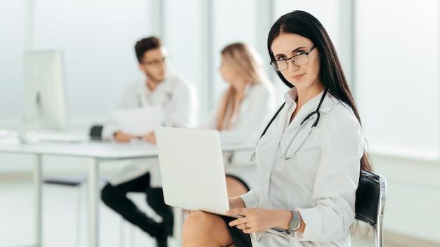 Terapeuta com um laptop sentado no escritório do hospital. foto com espaço de cópia