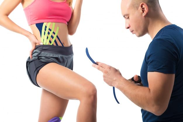 Terapeuta cuting kinesio fitas brilhantes na perna da mulher