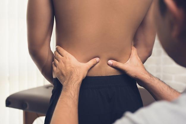 Terapeuta dando massagem ao paciente com dor nas costas na clínica