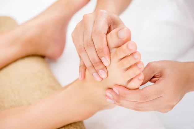 Terapeuta dando relaxante massagem de reflexologia tailandesa para uma mulher em spa