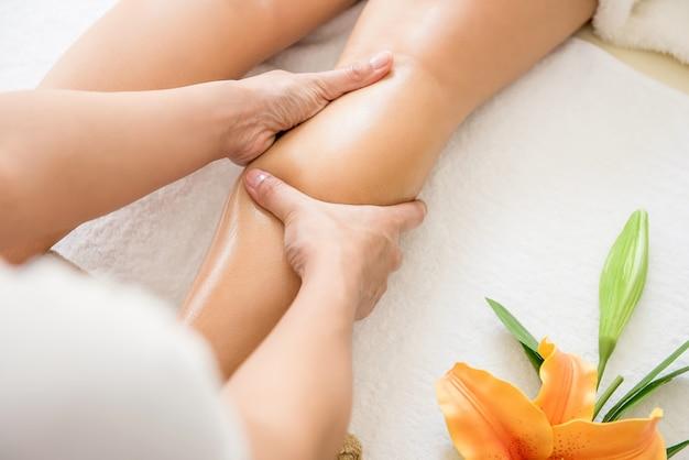 Terapeuta dando relaxante tratamento de massagem na perna de óleo tailandês para uma mulher no spa