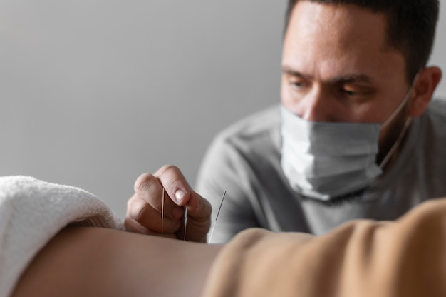 Terapeuta de close-up usando máscara médica
