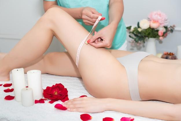 Terapeuta de massagem feminina fazendo massagem anticelulite, jovem. mede o tamanho da fita métrica do corpo.