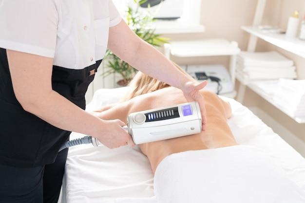 Terapeuta de massagem irreconhecível de pé na mesa de procedimentos e massageando profundamente uma mulher nua com dispositivo de lipomassagem
