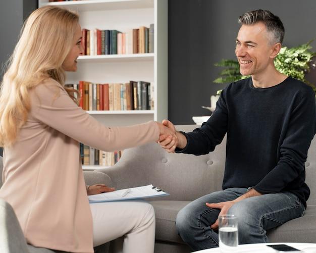 Terapeuta de mulher no meio do tiro apertando a mão de um homem