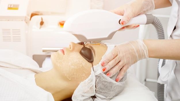 Terapeuta de salão de beleza em luvas remove cabelo com laser