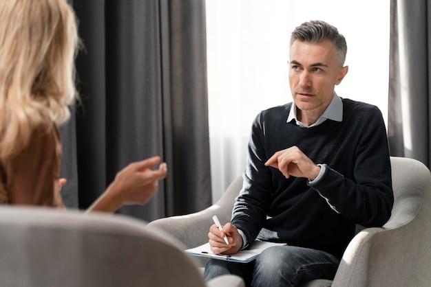 Terapeuta de tiro médio com prancheta olhando para o paciente