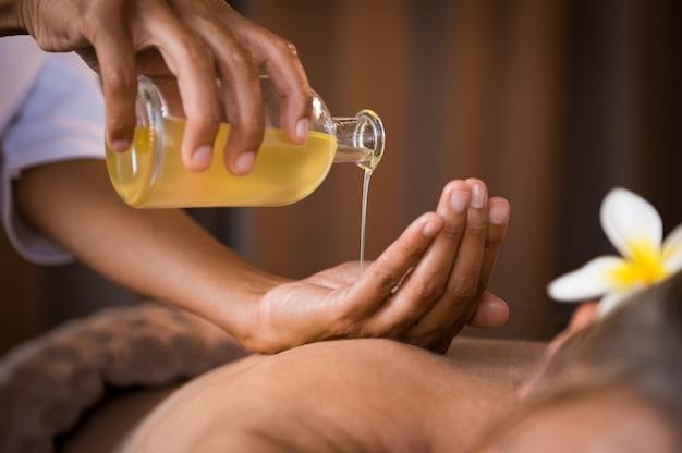 Terapeuta, derramando óleo de massagem no spa
