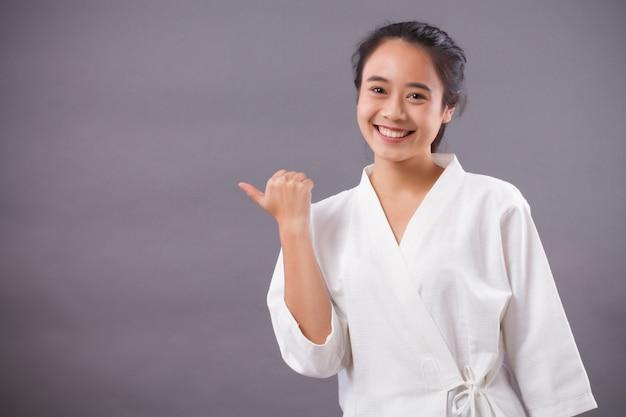 Terapeuta do spa da mulher apontando para cima; mulher asiática terapeuta de spa, trabalhador de spa, equipe de estética aponta para o espaço em branco