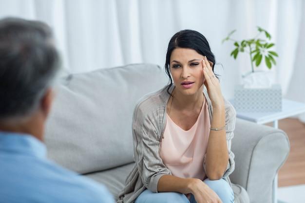 Terapeuta falando com mulher preocupada em casa