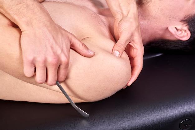 Terapeuta fazendo fibrólise diatoceante, dos ganchos curando o tratamento nas costas do homem.