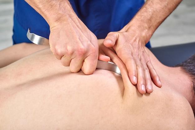 Terapeuta fazendo fibrólise diatoceante, dos ganchos curando tratamento nas costas do homem